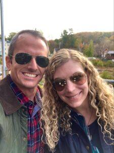 Sarah and her partner, Graham, smiling for an autumn photograph